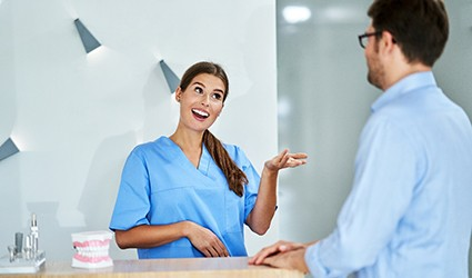 A dental receptionist discussing scheduling and dental insurance with a male patient