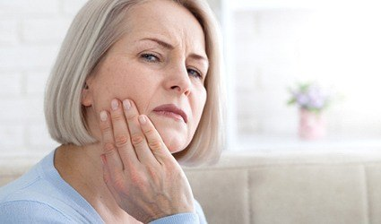 Older woman rubbing jaw due to dental implant pain