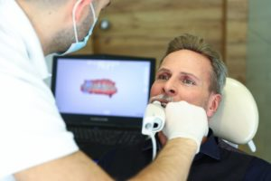 a dentist using a handheld camera device on a male patient's mouth