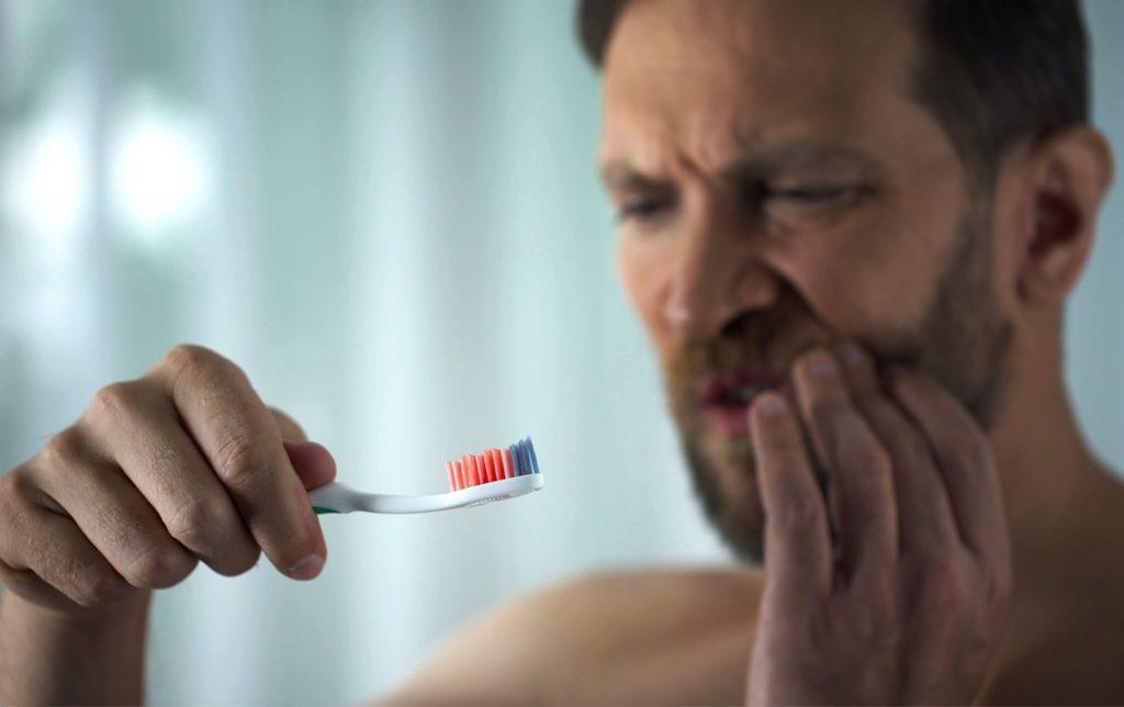 Man with bleeding gums brushing his teeth